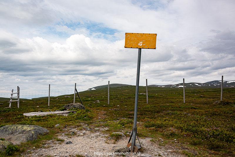 """Sliten gul skylt med texten """"Norge""""."""