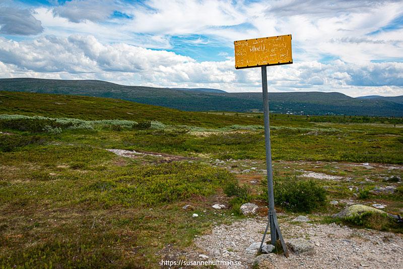 Sliten gul skylt där man nätt och jämt kan ana att det står Sverige.