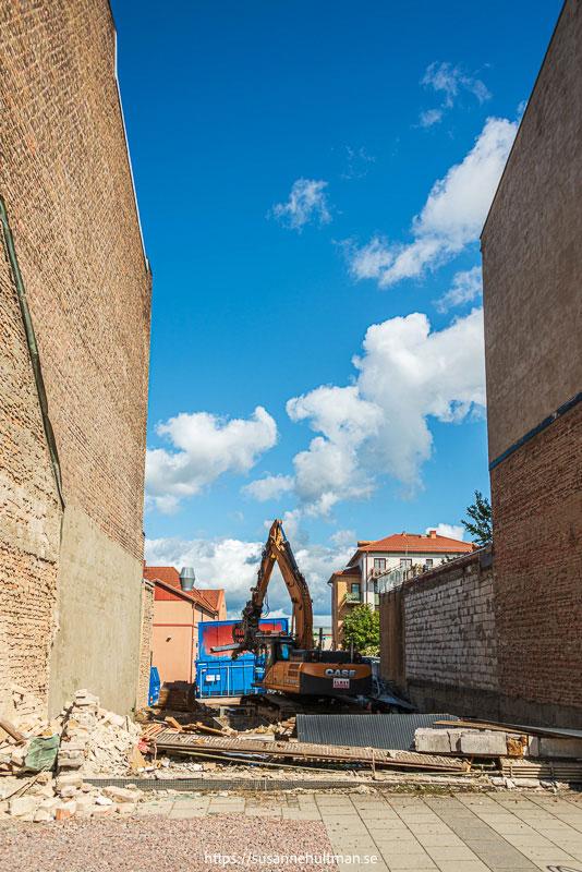 Grävskopa i lucka mellan två byggnader.