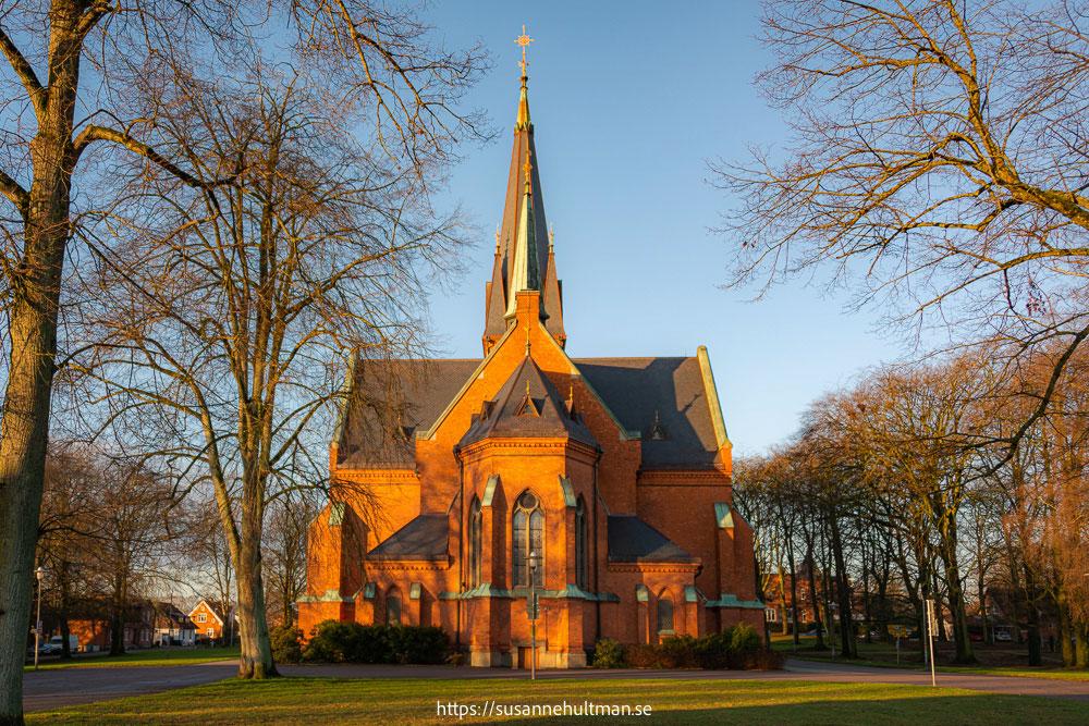 Eslövs kyrka i sol och med grönt gräs framför.