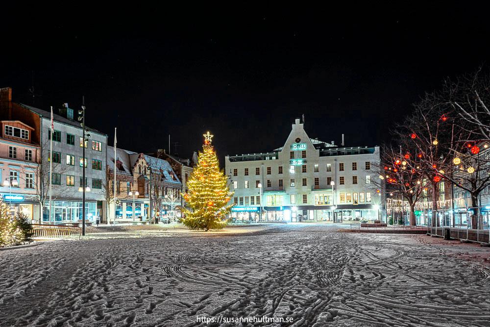 Kvällsbild av Stora torg med snö och julgran.