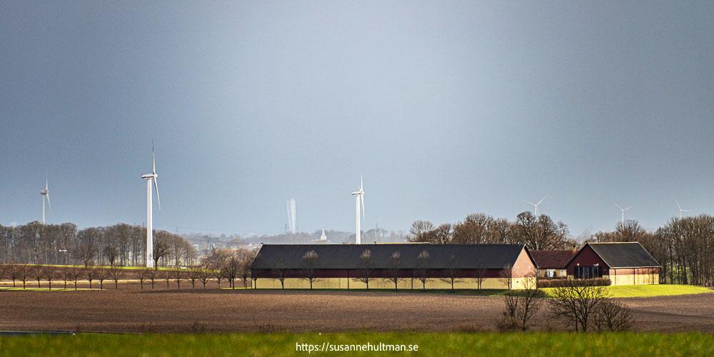 Turning torso i horisonten mellan vindkraftverk.