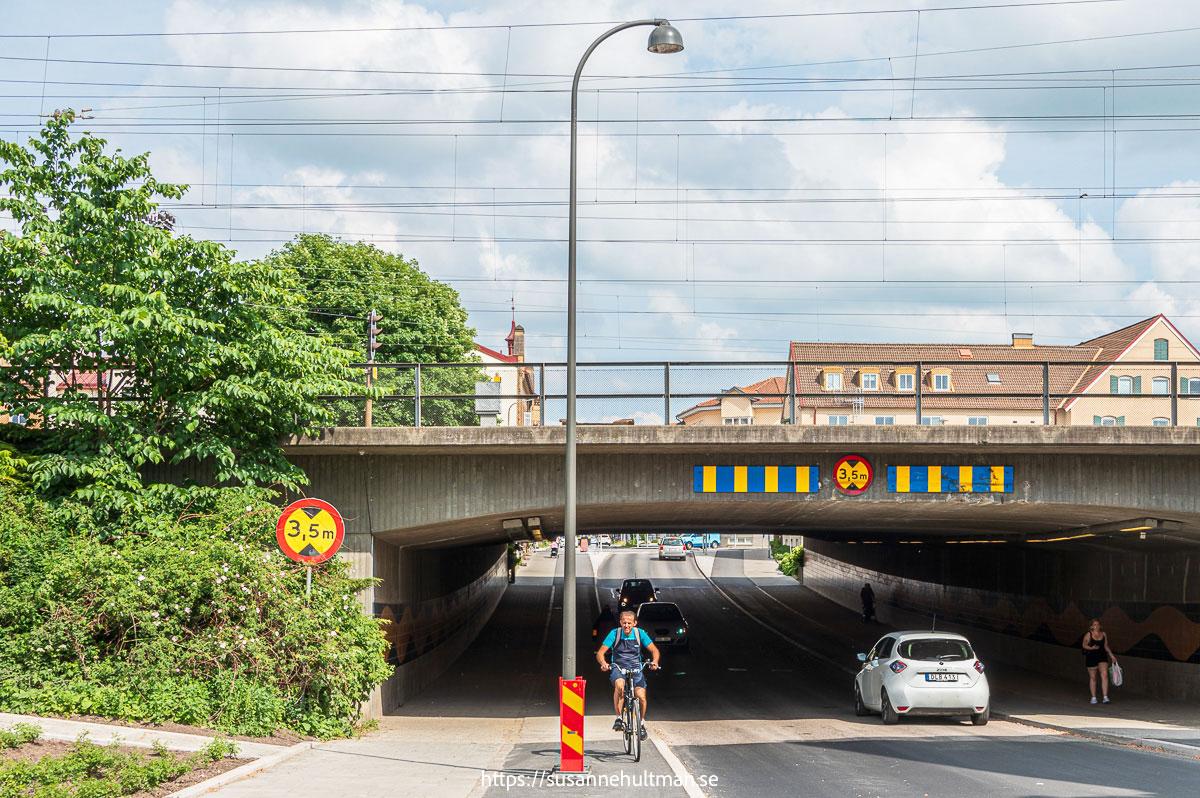 Nerfarten under järnvägsviadukten med cyklist vid lyktstolpen.
