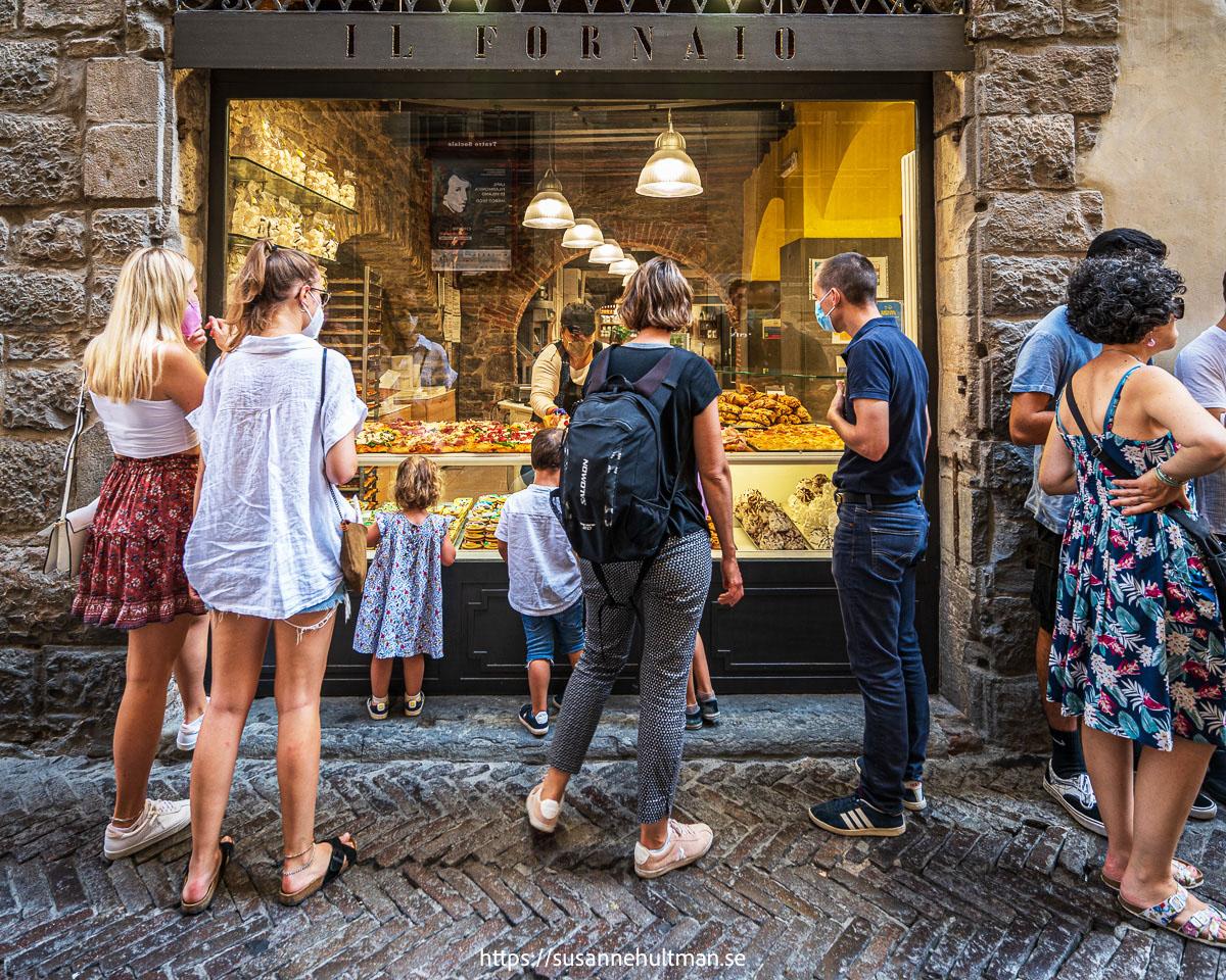Sommarklädda personer med munskydd tittar in i ett bageri.
